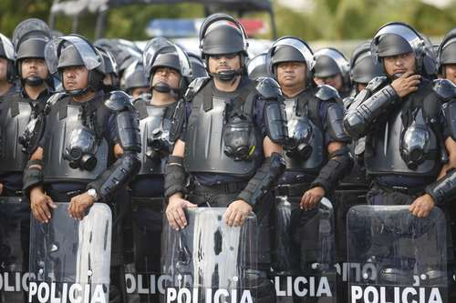 Agentes antimotines vigilan durante las negociaciones de la conferencia de CancúnFoto Carlos Ramos Mamahua