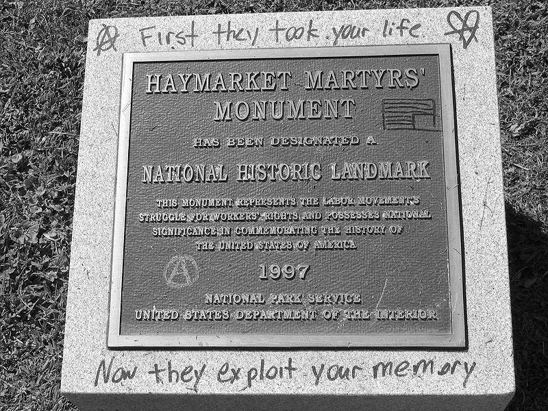 """Placa conmemorativa, colocada en 1997, por el Servicio Nacional de Parques de EE.UU. en Haymarquet.   En rotulador:la bandera norteamericana invertida y el texto:  """"Primero tomaron vuestras vidas, ahora explotan vuestra memoria""""."""