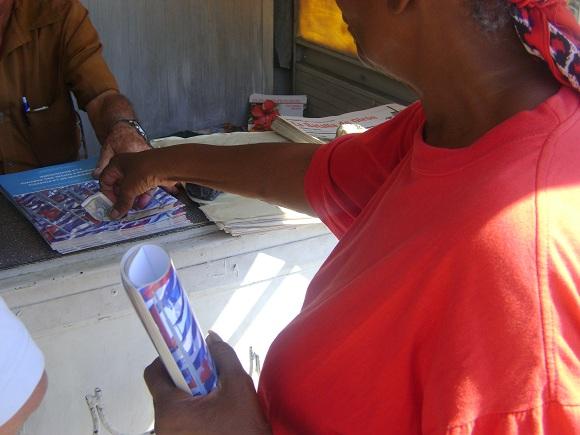 Cubana adquiere folletos con Lineamientos para el desarrollo económico y social del Partido y la Revolución en la Habana, Cuba