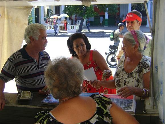 Cubanos adquieren folletos con Lineamientos para el desarrollo económico y social del Partido y la Revolución en la Habana, Cuba