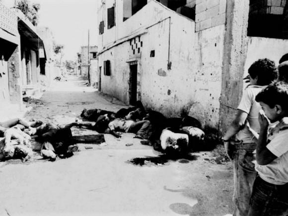 Niños palestinos contemplan cádaveres tras masacre israelí en Sabra y Chatila.
