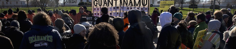 "People watch as protesters wearing orange jumpsuits depicting Guantanamo Bay detainees hold up a large sign reading ""Shut Down Guantanamo"" during a rally outside of the White House in Washington Monday, Jan. 11, 2016, calling for the closing of the detention center at the U.S. base at Guantanamo Bay, Cuba. (AP Photo/Carolyn Kaster)"