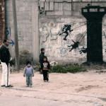 """«Gaza es a menudo descrita como """"la mayor prisión a cielo abierto del mundo"""", porque nadie tiene derecho a entrar o salir de ella. Sin embargo, es bastante injusto para con las prisiones: al menos ellas no tienen la electricidad o el agua potable cortadas sin razón casi todos los días ». Mural, foto y comentario de Banksy."""
